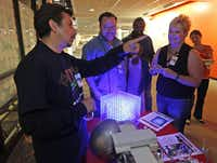 Luis Flores explains items he designed or built with TI equipment to Eddie Accomando of Dallas and Cindy Sheets of Garland.