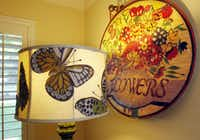 Butterflies adorn a lamp shade alongside a needlework tapestry of flowers.