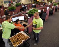 Scott Sasajima, left, passes a cookie to Chad Parmer, right, who gives it to Heather Modglin, center, as they take the cookie cart around the Texas811 office.