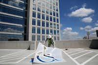 Enrique Acosta of Dallas paints a parking space atop the parking garage at the Granite Park IV office tower under construction in Plano. The 12-story tower, which will be ready in June, is leasing fast.( Photos by Andy Jacobsohn  -  Staff Photographer )
