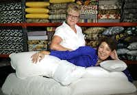 Deb Martz (left), owner of Chair Care Patio, and Merrimac Dillon, owner of The Pillow Bar, show off their finished goose down pillows in the Chair Care Patio workroom.
