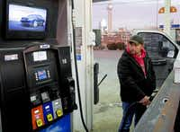 Jesus Herrera watches the gas pump, which is filling up tanks at prices not seen in years. How consumers and businesses spend the savings is what economists are watching.(Ron Baselice - Staff Photographer)