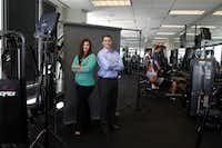 Katie Davis, Director of Finance, left, and Jeff Chesnut, President of Finance, pose in the Employees of Alliance Data's on site gym as fellow employees work out.