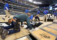 Work crews built a basketball court at Cowboys Stadium on Monday ahead of the South Regional semifinals of the 2013 NCAA Men's Basketball Championship this Friday. Practice sessions will be held Thursday. They're open to the public and admission is free.