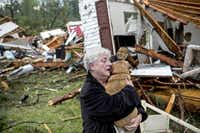 Constance Lambert clutched her dog Monday, thankful it was alive after she returned to her tornado-destroyed home in Tupelo, Miss. She had been at an event away from her home when the storm hit, but rushed home afterward to check on her pets.Brad Vest  -  The Commercial Appeal (Memphis, Tenn.)