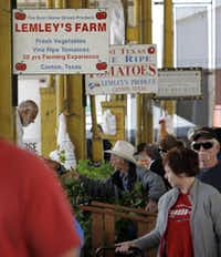 J.T. Lemley, center, of Lemley's Farm gathers tomato plants for a customer at the Lemley's Farm stand at the City of Dallas Farmers Market on North Pearl Street in Dallas on April 6, 2013.Sonya Hebert-Schwartz - Staff Photographer