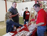 Mikayla Fox, 8, and her dad, Brian Fox, both of Kaufman, sample the toffee at the Texas Toffee stand at the city of Dallas Farmers Market on North Pearl Street in Dallas on April 6, 2013. At right is Derik Webb, co-owner, of Texas Toffee.(Sonya Hebert-Schwartz - Staff Photographer)