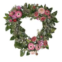 Gardenia foliage and seeded eucalyptus form the base of Cebolla's heart-shaped wreath. Florists then added accents of eucalyptus pods, ranunculus, freesia and mini gerbera daisies.( Photos by  Nathan Hunsinger  -   Staff Photographer )