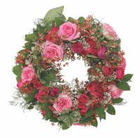 Florist Raquel Lovern of R Love Floral Designs in Addison included shades of pink roses, white wax flowers, lush tree fern sprigs and deep green salal leaves for her wreath.( Nathan Hunsinger  -  Staff Photographer )