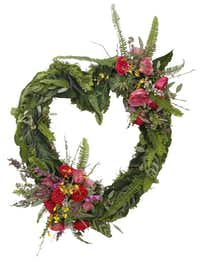 Moss, ferns and exotic plant leaves, field flowers, garden roses and succulents create a tropical romance in this wreath from Central Market florists.( Nathan Hunsinger  -  Staff Photographer )