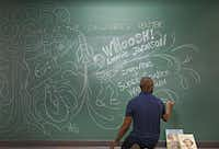 Illustrator Don Tate adds his autograph as he puts the final touch on his drawing on the large chalkboard in the children's area during the Dallas Book Festival.( Jae S. Lee  -  Staff Photographer )