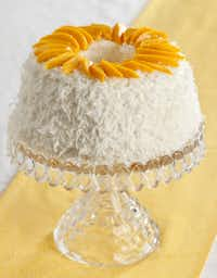A sunny ring of mango slices adorns the top of the Peach and Mango Coconut Cream Cake.