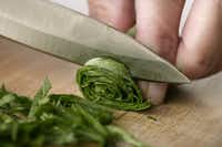 Making basil chiffonade. 3. Slice the basil roll into strips.