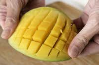 Trimming a mango. 3. Push the mango half up so that the cubes stand out.