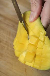Trimming a mango. 4. Cut the mango cubes away from the peel.