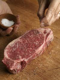 Seasoning a New York strip steak.