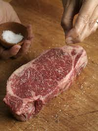 Seasoning a New York strip steak.