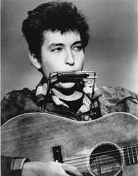 Folk singer and songwriter Bob Dylan plays the harmonica and acoustic guitar in this 1963 file photo.