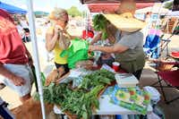 Loraine Jarocki, left, of Dallas purchases greens from a vendor at the White Rock Local Market, on Sept. 07, 2013.