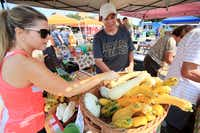 Ashley Dudley, left, purchases squash from Sofia Martinez at the Rae Lili Farm booth, at the White Rock Local Market, on Sept. 07, 2013 in Dallas.