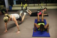 In a TRX class, participants put various body appendages into its canvas slings to exercise.