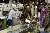 Recon Militaria owner D.J. Goodwin (left) trades stories with Clay Krakora, who picked up a photograph from the store on Garland Road.