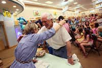 "Polly Holyoke gets a congratulatory hug from by longtime friend and colleague Joe Chicoskie of Plano, during a book signing for ""Neptune Project"" at a Barnes & Noble in Plano."