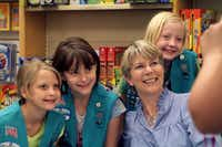 Girl Scouts Lindsay McClain (from  left),  Emily Oefinger and Mabrey get a snapshot with Plano author Polly Holyoke.
