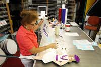 """""""The Sign Lady"""" Cindy Villela, peels away decal paper while applying letters to a drill/dance team sign at her home workshop, on June 20, 2012 in Richardson. This particular sign, which is made for a drill team member, is very labor intensive and normally takes about a month to complete. The sign requires five coats of paint of various types. The different colors are used to match eyes, skin, and hair of the dance member. Villela started carpentry at age 10 and now has a successful 15-year-old business making handmade figural spirit signs for area schools."""