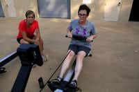 Lisa Henry,left, works with Paige Mosley while she uses an ergometer during the Adaptive Rowing program at White Rock Boathouse on White Rock Lake on July 31, 2013 in Dallas. The program trains people who have a physical disability to row. The participants learn adaptive erging on land first followed by sculling on the water.