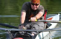 John Cage rows during the Adaptive Rowing program at White Rock Boathouse on White Rock Lake on July 31, 2013 in Dallas. Cage was paralyzed last year as a result of West Nile virus. The program trains people who have a physical disability to row. The participants learn adaptive erging on land first followed by sculling on the water.
