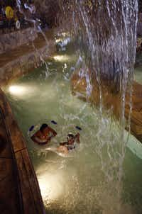 A mother and daughter float under a waterfall in the lazy river at Great Wolf Lodge.Mark Rogers