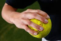 A University of North Texas softball player shows the improper way grip the softball to throw, Thursday, March 21, 2013.