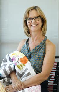 Michelle Kitto of Urban Spools Sewing Lounge cradles a modern quilt she made and named after her daughter Abby.(Tom Fox)