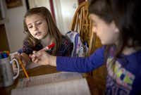 Molly Kahlig (left) helps her sister, Lucy, with a math problem. The children eat breakfast, then start with handwriting and math, followed by other subjects. They break for lunch and study more subjects in the afternoon.( Staff photo by G.J. MCCARTHY  - DMN)