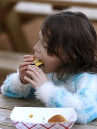 Kailey Reyes, 7, eats a burger at Richardson Food Truck Park on Saturday.(Jae S. Lee - Staff Photographer)