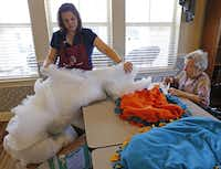 Brandy White-Burda hands dog bed filler to Jane Byrnes and others working on making the bed at Mustang Creek Estates of Frisco. The dog beds will be donated to the Frisco Humane Society.( Staff photo by VERNON BRYANT   -  DMN )