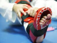 Evita Nino, 9, puts on pads before practice. The USA Taekwondo National Team is headed to Roana, Italy, next month to compete in the 2015 World Taekwon-do Championships.( Staff photo by Andy Jacobsohn  -  DMN )