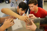 Josh Nelson (left), 16, and Richard Rensing, 16, both of McKinney Boyd High School students, work with other students on assembling the forward lower firewall and fuselage of a Van's RV-12 aircraft during a class period of the McKinney Aviation Academy at McKinney National Airport.(Staff photo by ANDY JACOBSOHN - DMN)