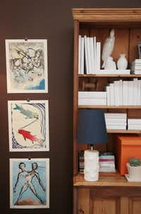 An oversized pine cabinet is dressed in white accessories, which lets zodiac artwork shine in the vignette from John Phifer Marrs. The room is accented with pops of orange and teal.