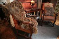 Peacock Alley's bedroom is loaded with texture, including a feathered throw and pillow that dress a pair of leather and upholstered chairs.