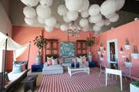 Laura Lee Clark's coral setting gets a boost of drama from the paper lantern collection, oversized vases atop side tables, white shelving and the canopy over the indoor/outdoor daybed.