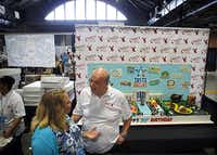 Carlo's Bake Shop head decorator Mauro Castano (left) visits with Kristin Lavitola of Grand Prairie in the Foodie Experience during the Taste of Dallas at Fair Park in Dallas, Saturday, June 4, 2016. The Carlo's Bake Shop, owned by the Cake Boss, Buddy Valastro, has a new location on Preston Rd. in Dallas. (Tom Fox/The Dallas Morning News)