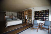 Cecilia Boone tucks items into the bookshelves of a master bedroom whose design forgoes bedside tables. Buddy the dog plays fashion accessory on the Jonah bed.