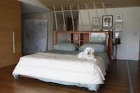 The rib of a fish that Garrett Boone spotted on a shore was part of the inspiration for his Jonah bed, guarded by Buddy. Because of its odd shape, the bed is literally the centerpiece of the master bedroom.