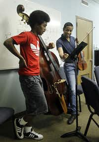 Marcus Pyle, a 23-year-old Juilliard student from Garland (right), helps bass player Daniel Bloch, 15, at Pyle's ChamberWorks music camp at First United Methodist Church in Garland.