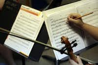 Violinist Tien Huynh, 16, makes notes on her music. ChamberWorks founder Marcus Pyle launched the camp in 2010 with help from two musician friends.