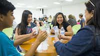 Alex Paniagua (left), Mariah Ann, Calista Martinez and Calette Benavidez play cards during a community barbecue for Innovation, Design and Entrepreneurship Academy at Fannin High School in Dallas.( Staff photos by Ashley Landis  - Staff Photographer)
