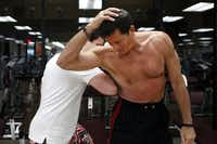 Ted Gambordella demonstrates how his son Teddy Gambordella punches him in his abdominal area at Dallas Lifetime Athletic in Dallas on Friday, February 15, 2013. He will celebrate his 65th birthday on the 22nd by doing his 6 millionth crunch.