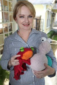 Sharon Miller of University Park holds two of her creations at the Shabby Sheep, which is coordinating a yarn bombing for the opening of the Klyde Warren Park.